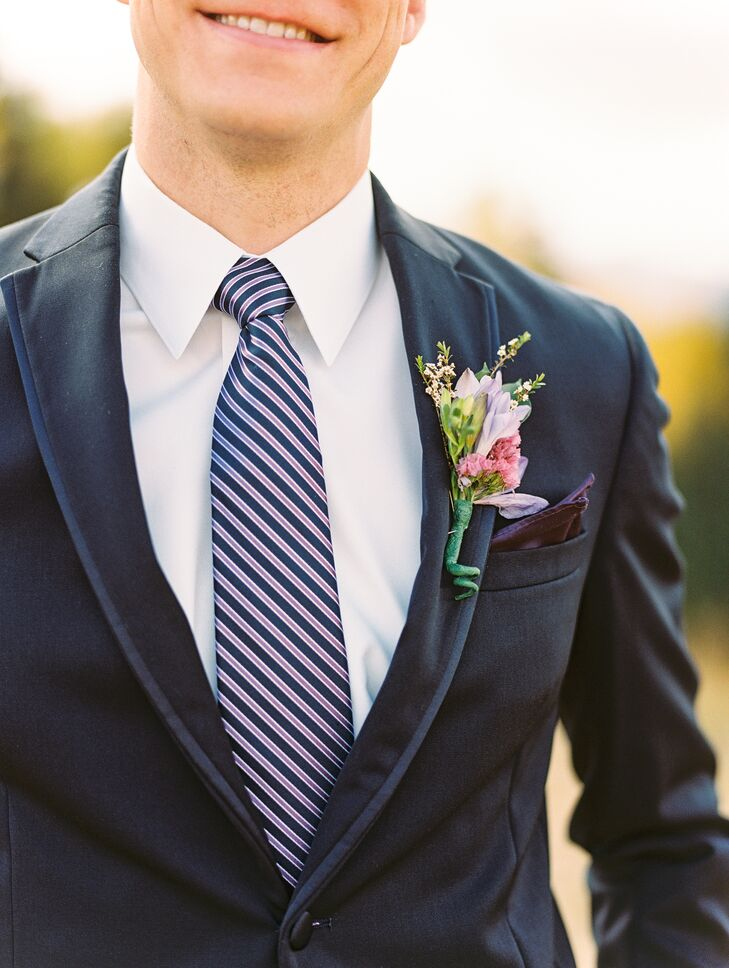 Groomsmen sported deep navy suits with striped ties and boutonnieres made with vibrant pink blossoms.