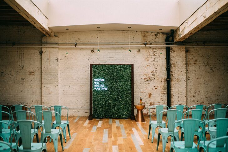 The Joinery's Industrial Ceremony Space with Blue Bistro Chairs and Greenery Backdrop