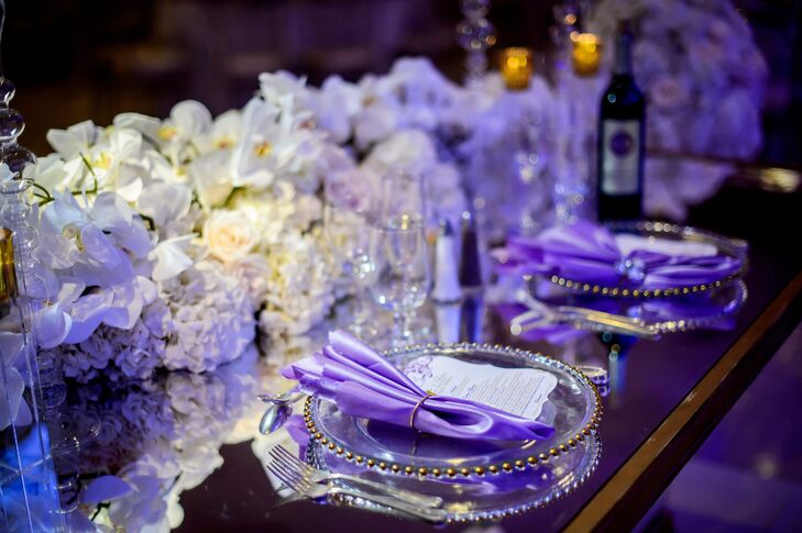 Pops of purple played into the evening's ultra-glam aesthetic. Long lengths of romantic ivory blooms graced the tops of the long mirrored tables, with lavender linens and silver beaded chargers amplifying the effect.
