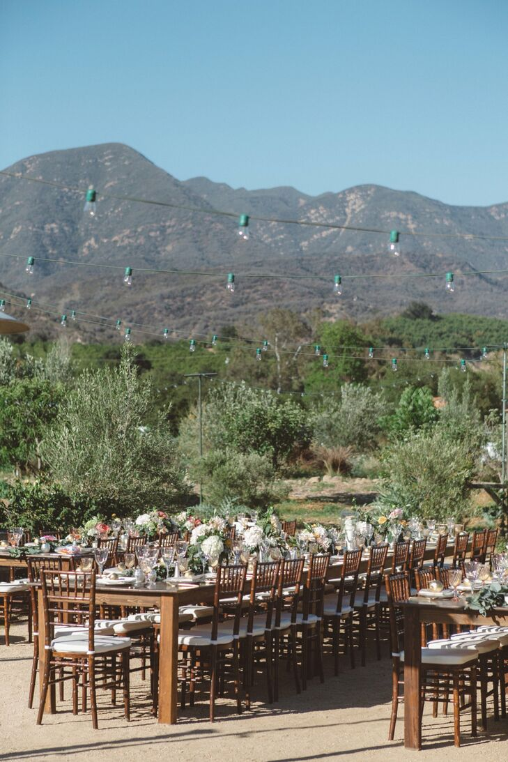 This outdoor reception was designed to highlight the natural beauty of the setting in Ojai, California. Guests sat at long wooden tables under market lights.