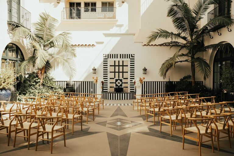 Rooftop ceremony with wood wishbone chairs and palm trees