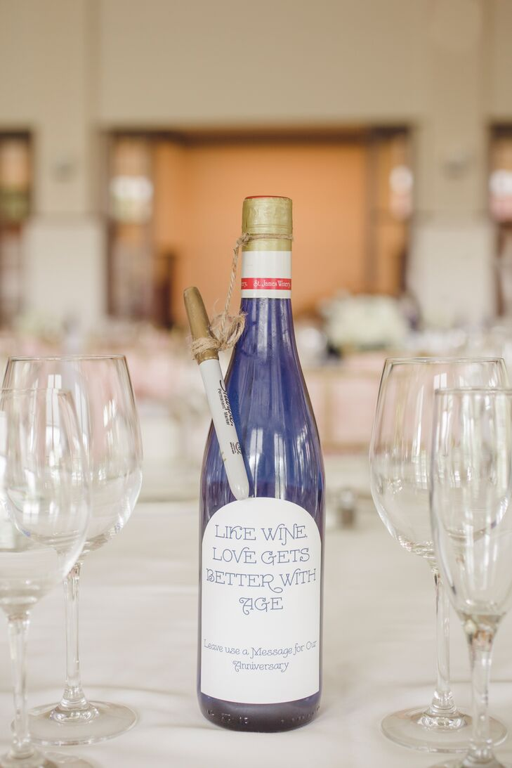 Instead of table numbers, each table had a bottle of wine and a gold pen for guests to leave messages. The couple plan to drink the corresponding wine bottle for each anniversary.