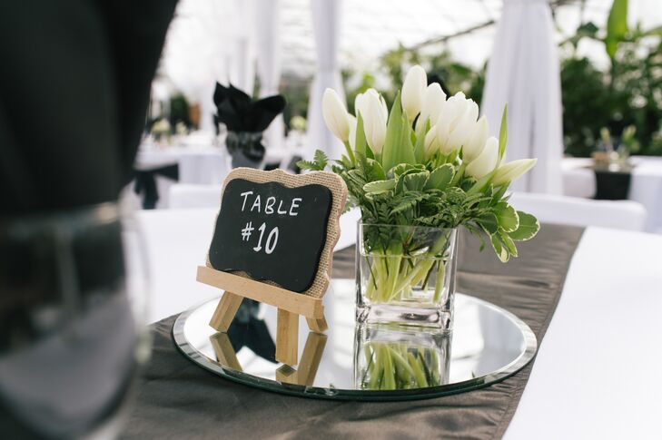 A short, clear vase of fresh white tulips and a chalkboard mini-easel table number were displayed on a mirror for the romantic centerpiece decor.