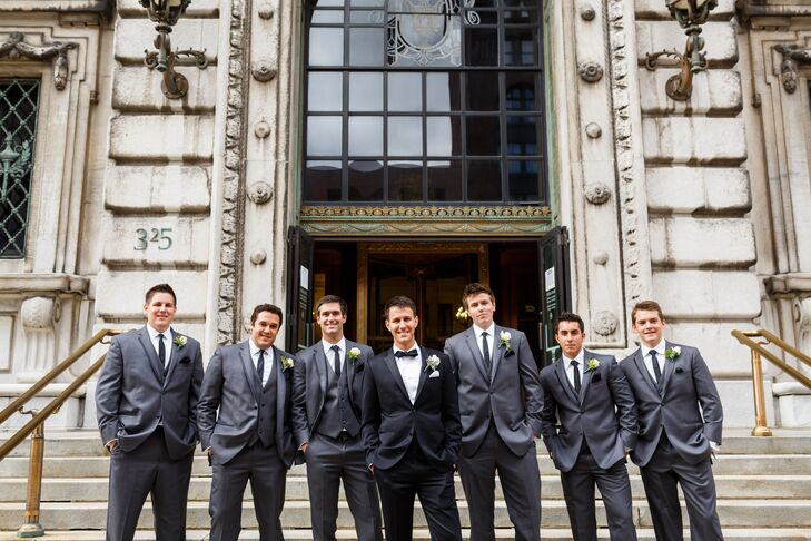 Ryan wore a black tuxedo designed by Indochino with a black bow tie to match. His groomsmen stood beside him, wearing gray tuxedos with matching ties from Black by Vera Wang.