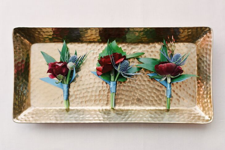 "The crimson boutonnieres reflected the day's romantic, moody jewel tones. ""We're definitely not afraid to play with color, so we went with the loveliest jewel-tone hues in slate and indigo, blush, ivory, vintage gold and splashes of deep merlot and burgundy,"" Tammie says."