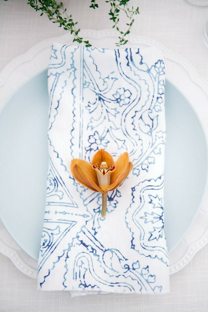 Modern Place Setting with Blue Charger, Patterned Napkin and Orange Orchid