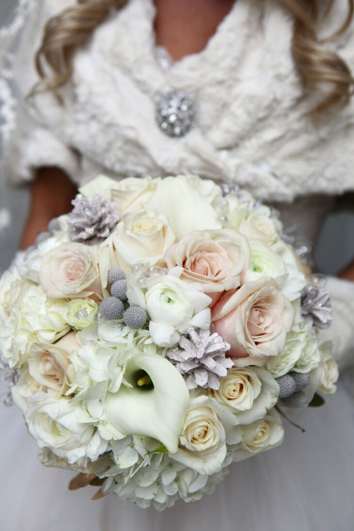 Lisa held an ivory, purple and pink bouquet filled with calla lilies, roses and silver brunia, which was arranged by Flowers on Orchard Lane. The flowers complemented the winter-themed color palette, made up of champagne, gold, silver and neutral colors.