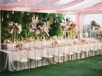 Boho wedding tent decorations with pampas grass centerpieces, colored drapes and Edison bulb lights