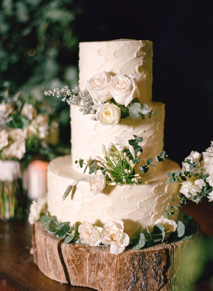 Charlotte and Jeff offered guests a simple vanilla cake with vanilla buttercream, decorated with fresh flowers and greenery. To accent the rustic barn location, Devil's Thumb Ranch in Tabernash, Colorado, the cake sat on a hand-cut wooden log.