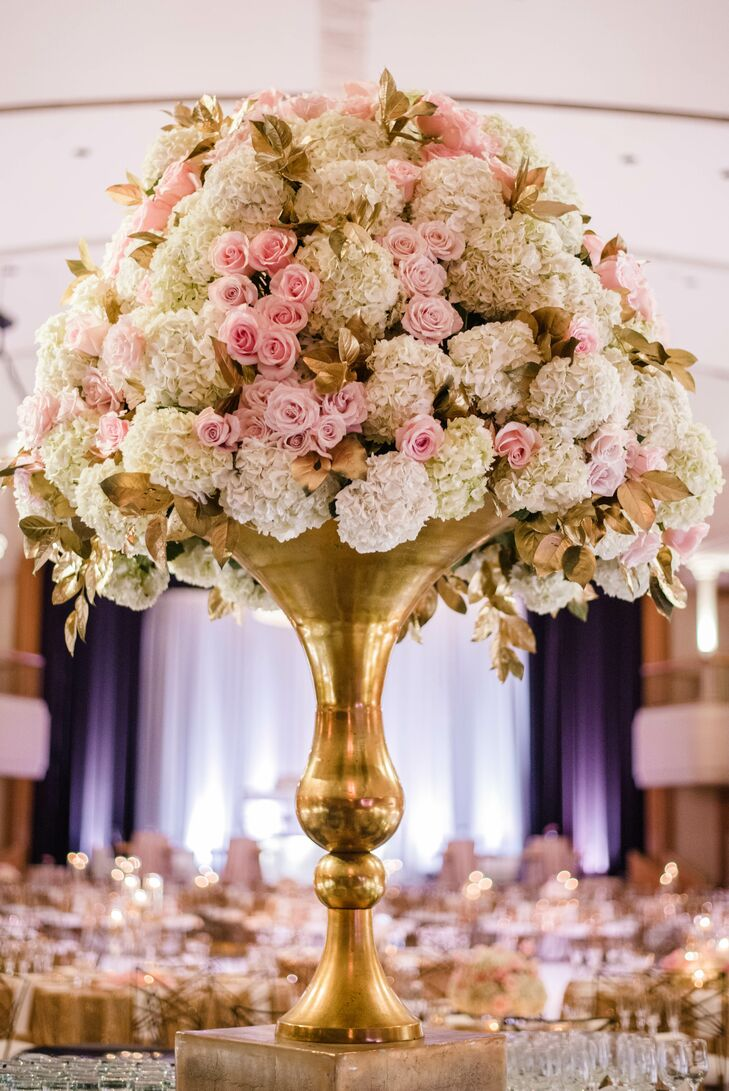 Dramatic floral arrangements featured white hydrangeas and blush roses overflowing from  oversize gold vases.