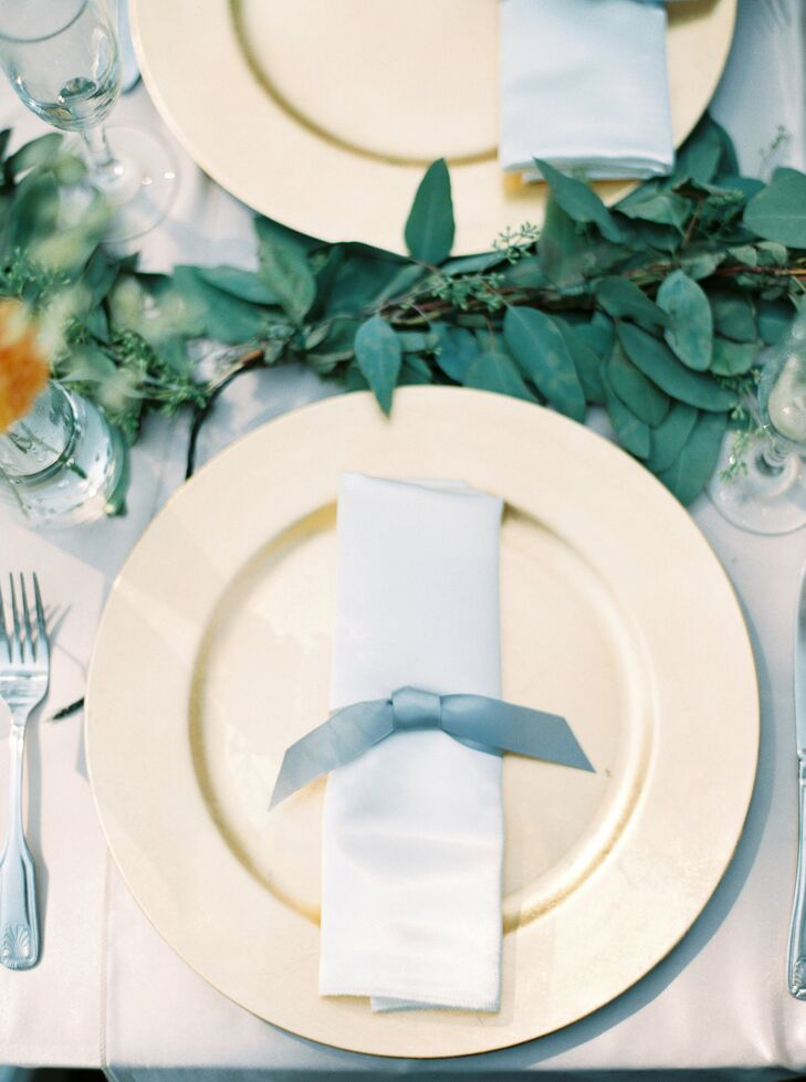 Sprigs of leafy greenery brought the garden vibe to the dining tables, which were set with elegant gold plates.