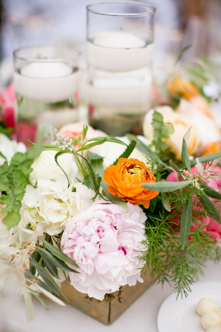 As the day progressed from ceremony to reception, color was added to the decor through bright florals. Orange, pink and white were used in the centerpieces, which featured a small wooden box and floating votive candles.