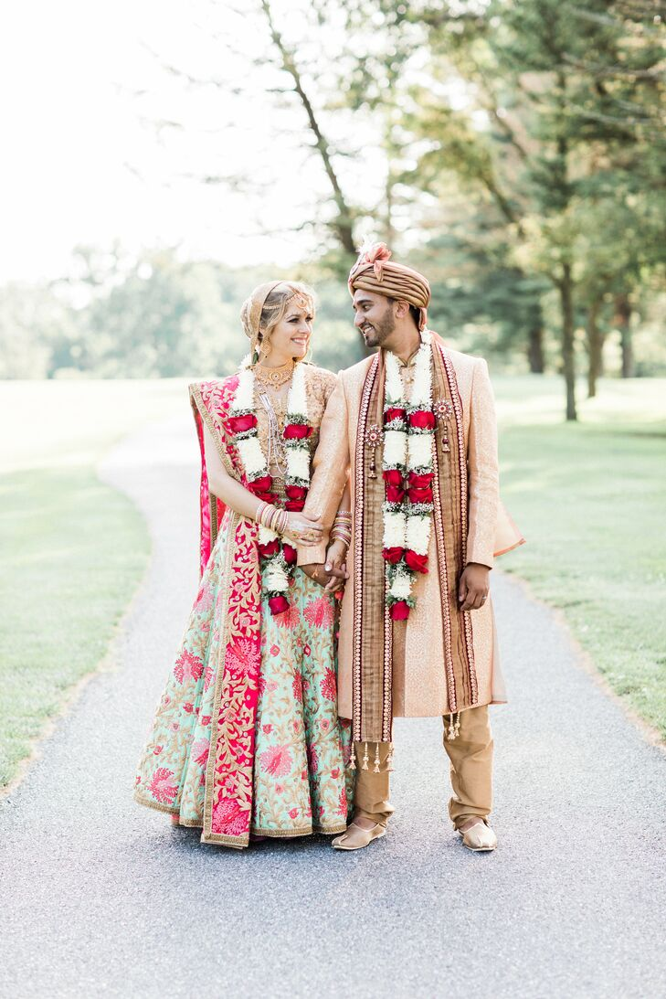 "For their second Hindu ceremony, Arselie and Vikas wore traditional clothing. ""My lehenga consisted of an embroidered gold top was a greenish blue with pink flower accents and a matching scarf,"" says Arselie. ""I was decorated head to toe in the most gorgeous traditional Indian jewelry, and I loved my headpiece so much I wore it the entire night!"""