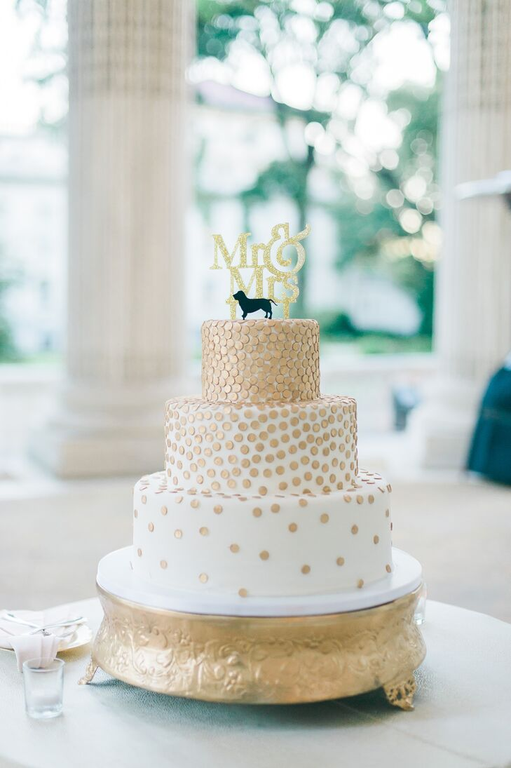 The wedding cake was flavored with strawberry cream and chocolate hazelnut. It was decorated in gold and featured a basset hound topper that represented Erin and John's pet dog.