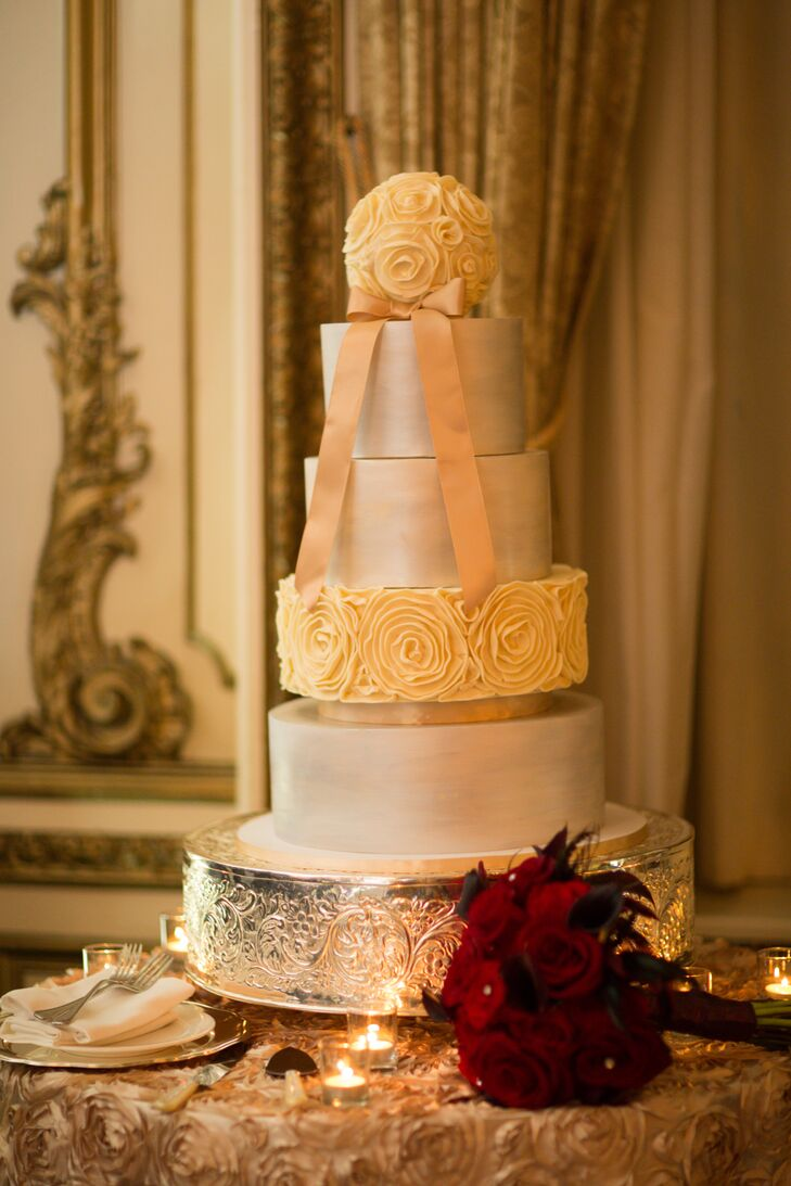 The four-tier wedding cake had three layers decorated with metallic silver, and one layer with a cream rosette pattern. A flower ball made of cream was the topper for the wedding cake, decorated with a pink ribbon positioned in front.