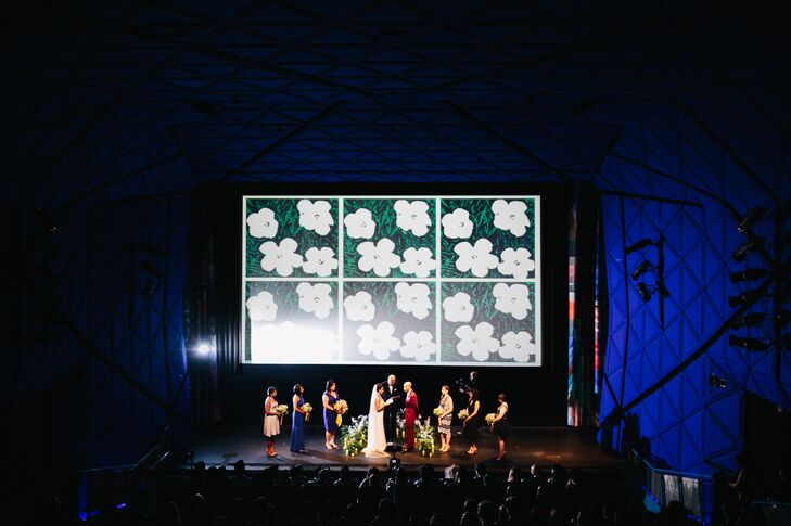 """""""Because the ceremony was in a movie theater, we kept the decor pretty simple,"""" Adam says. """"We had to keep in mind that we would be using the movie screen to play videos, so our florist designed a beautiful open circle that was low to the ground but still brought drama."""""""