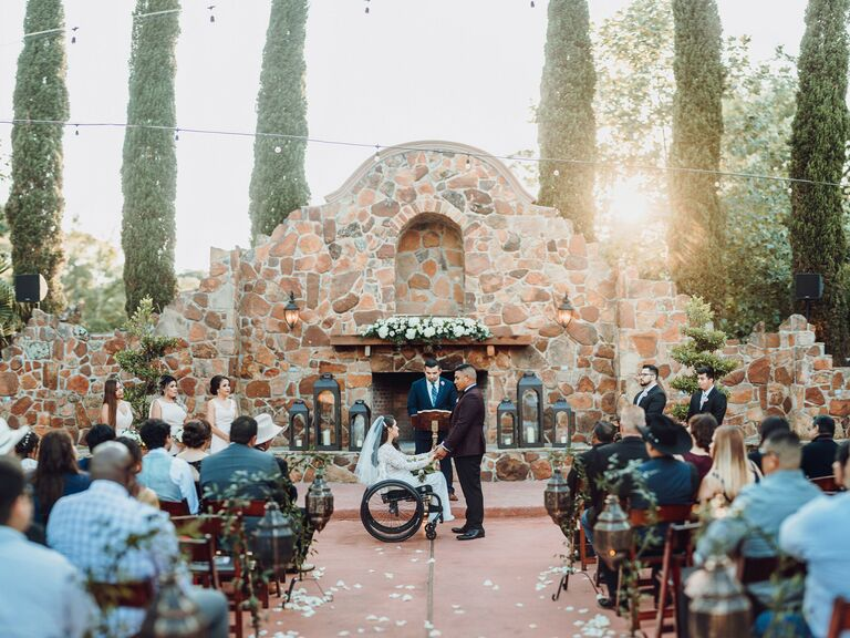 wedding officiant couple holding hands in front of guests
