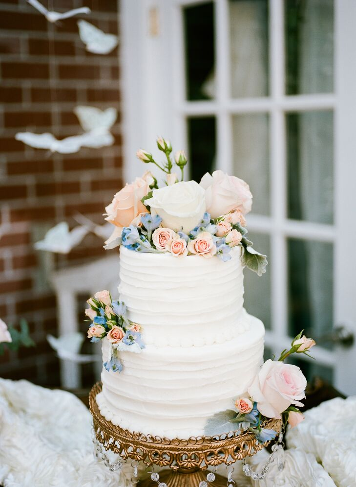 The textured buttercream wedding cake was decorated with fresh roses in blush and ivory, blue hydrangeas and dusty miller.