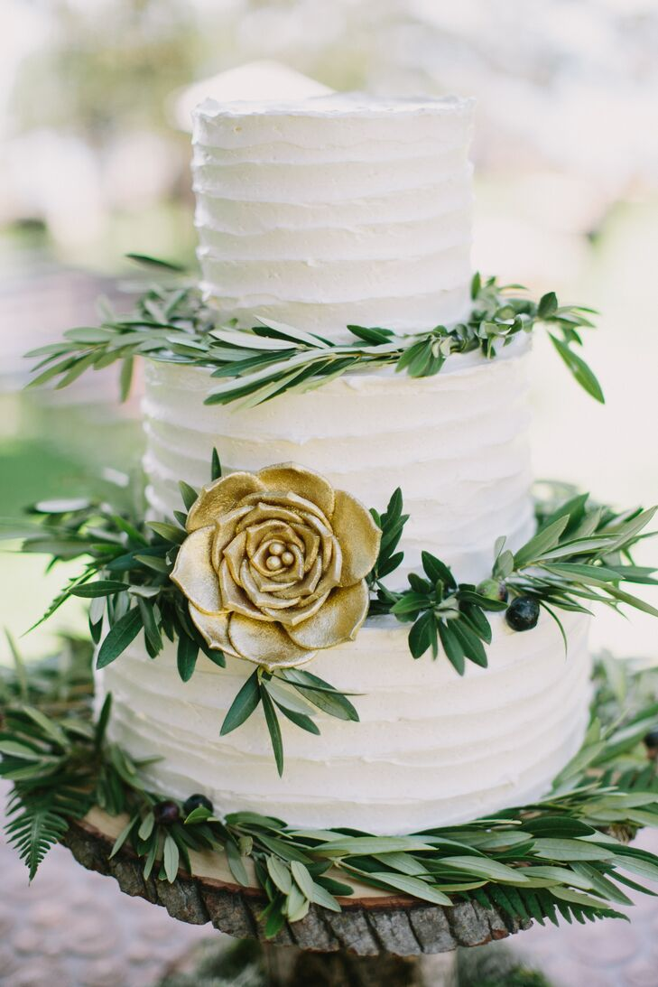Local baker Edith Meyer crafted a three-tier, horizontally rough-frosted cake with layers of bittersweet chocolate with strawberry buttercream. The base of each tier was encircled with fresh olive branches, with a large gold marzipan succulent offset on the center tier.