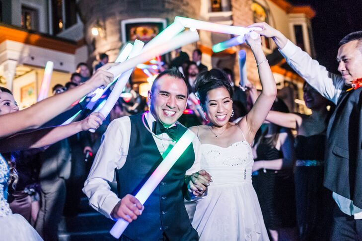 Bride And Groom Gracefully Exit Under A Foam Glow Stick Arch