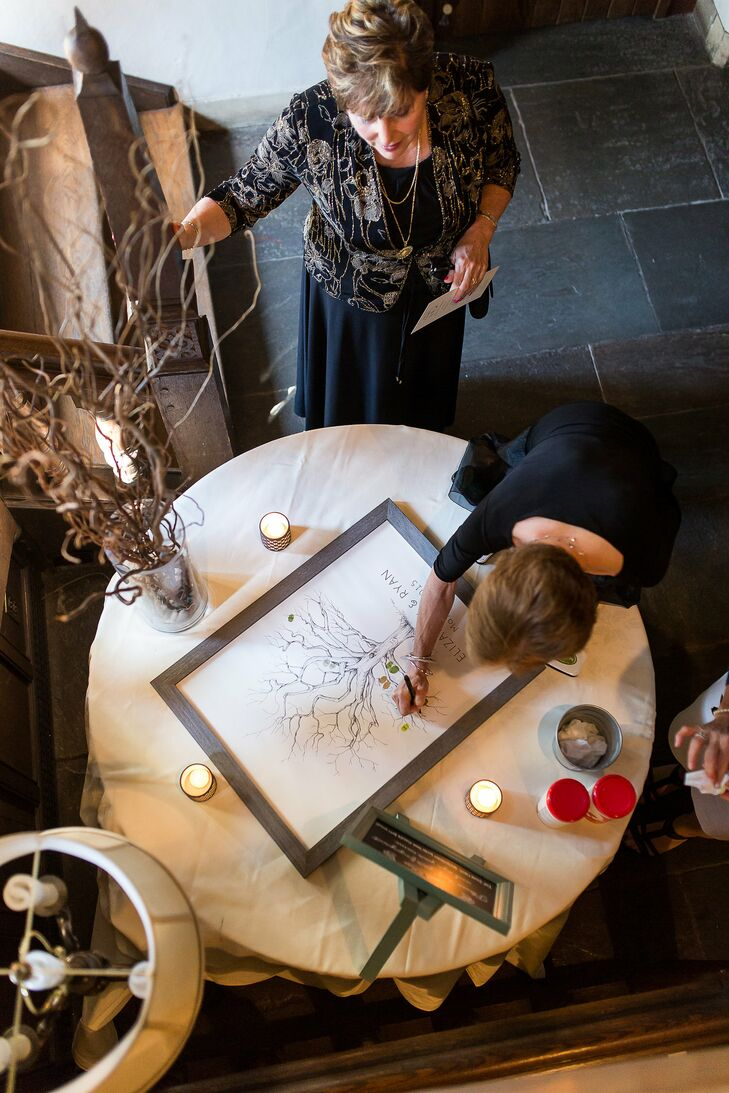 Instead of a traditional guest book, Liz and Ryan had their guests sign a framed tree poster. They also had their guests add their thumbprints to the trees to make up the leaves.