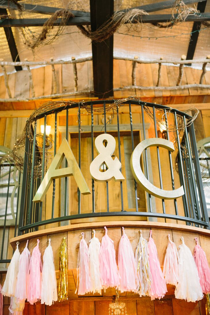 """""""I had a lot of DIY help from my crafty bridesmaids,"""" Aja says. Decor including a memory board, a gold glitter Friday """"F"""" sign and custom tassels brightened the rustic barn along with the romantic color palette."""