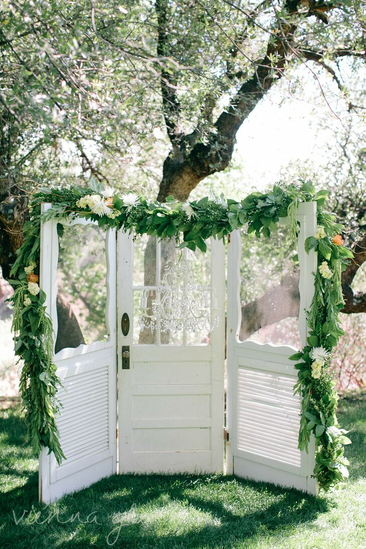 Three reclaimed vintage doors lavishly decorated with an elegant floral swag and chandelier served as the backdrop for the ceremony.