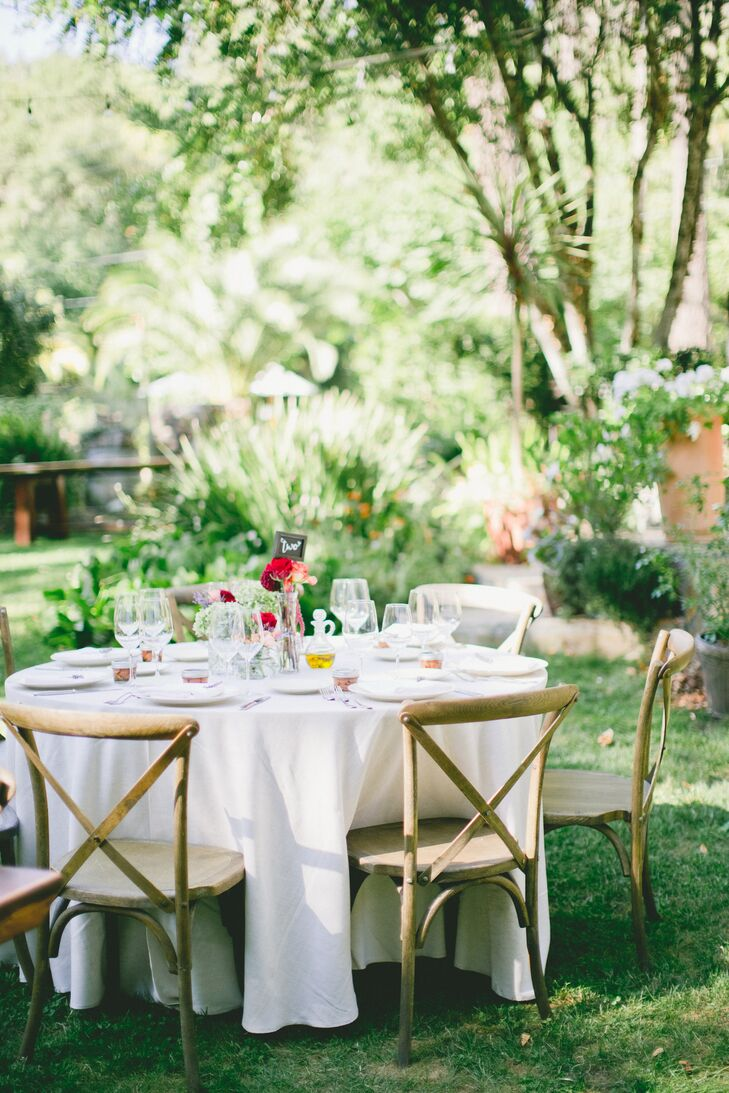 Ivory linens and wooden chairs gave the couple's alfresco reception a laid-back vibe.