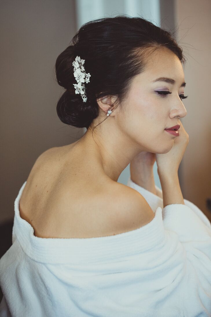 Dongli wore an elegant beaded clip with a flower design on the right side of her updo hairstyle. She wore simple pearl stud earrings to go with the hair accessory.
