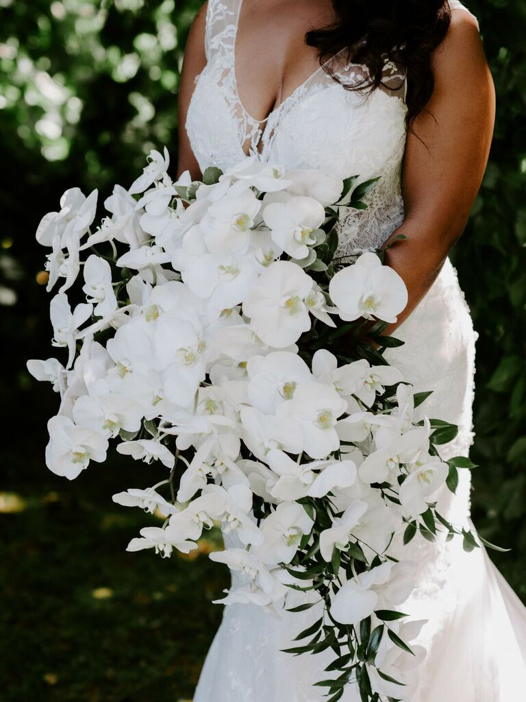 most popular wedding colors bride holding white orchid bouquet in white dress