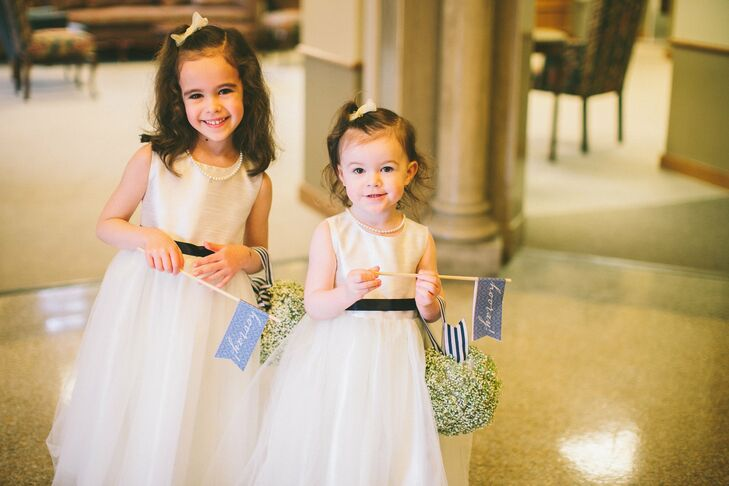 The flower girls wore fluffy white dresses accented with a navy ribbon.