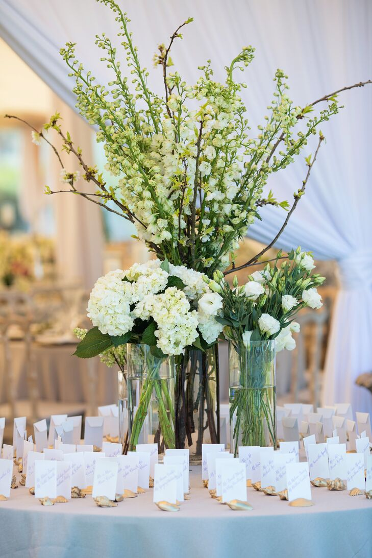 To inject an element of drama into the escort card display, Botanica International Design Studio centered the golden seashell card holders on a trio of hurricane vases overflowing with delphiniums, branches, hydrangeas and lisianthus in bright shades of green and white.