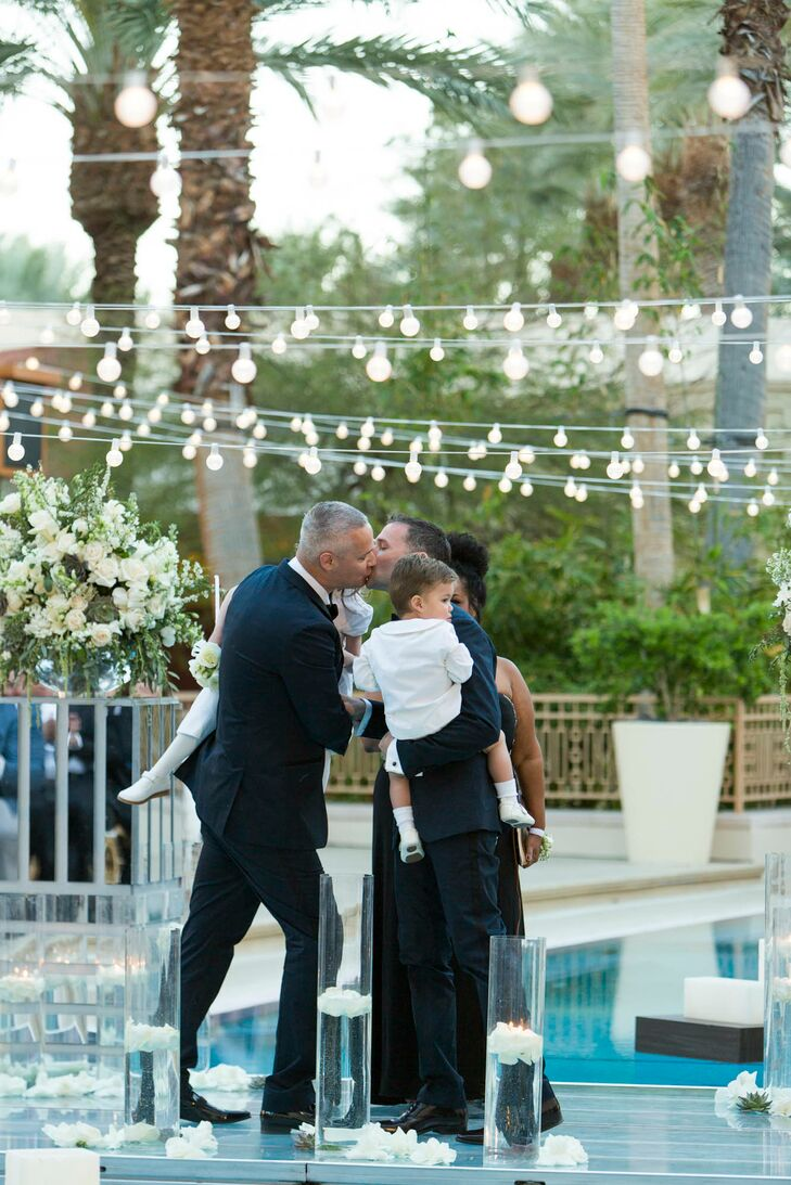 Greg and Fletcher share their first kiss as a married couple while holding their two children. It was important for them to be included on the day, so they were present while the pair got ready and for most of the night.