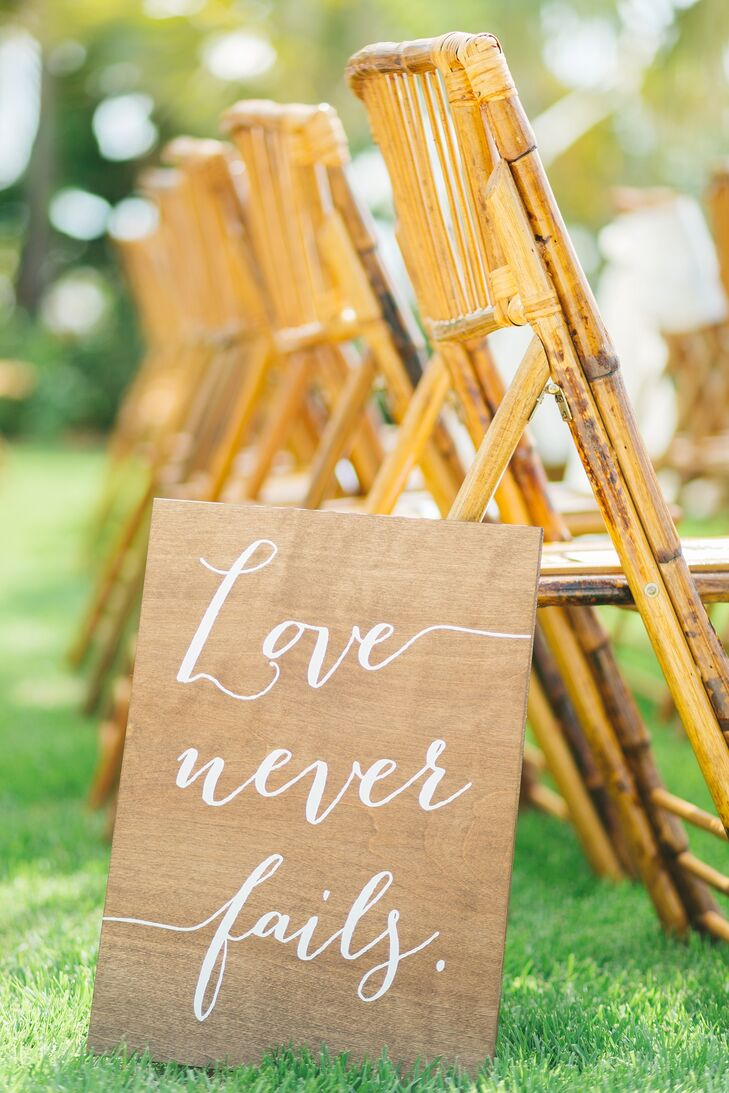 Kay and Ben decorated their waterfront wedding site with bamboo chairs, white roses and wood signs.