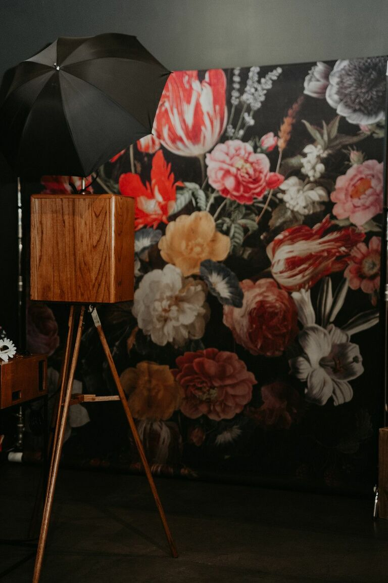 Vintage photo booth with floral wallpaper backdrop