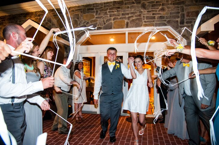 As Haley and Jeremiah exited the reception, guests stood on both sides of them waving white ribbons on sticks in celebration of their marriage. Haley changed into a more casual white cocktail dress with a V-neck for the reception.