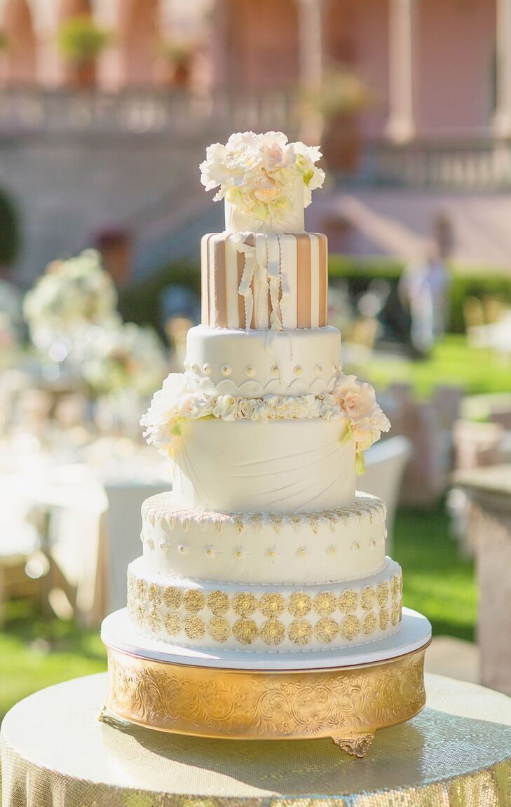 The couple served a grand six-tier wedding cake baked by Cakes by Ron. The berry chantilly cake was covered with blush and ivory sugar flowers, fondant, gold accents and intricate details on every tier.