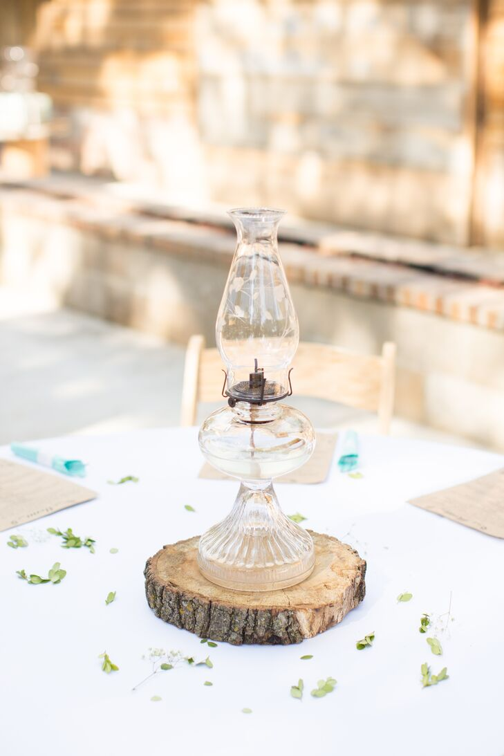 Simple centerpieces featured vintage oil lamps atop rustic tree-trunk slices.