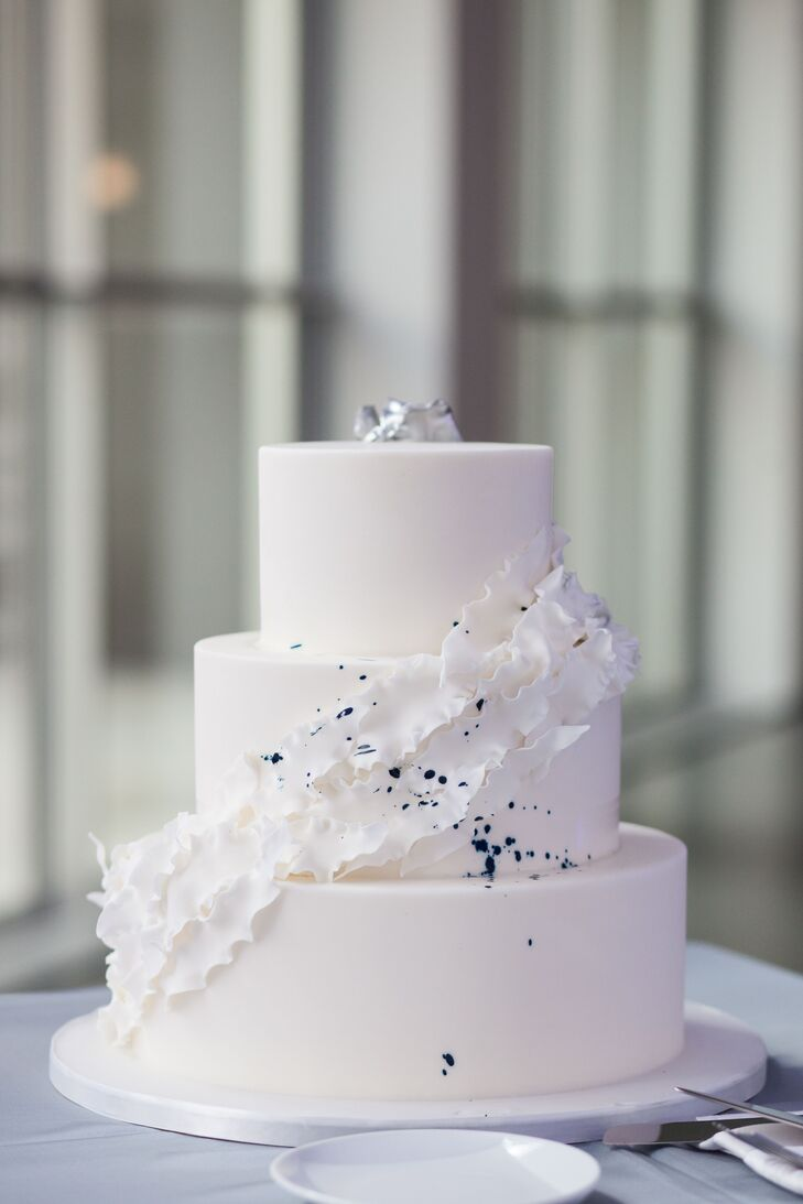 "In order to achieve the perfect shade of white, the cake designer used fondant to create a ruffle effect ""that spiraled up the cake in silver,"" Justin says. ""We had a spatter of blue ink across the cake to finish things off."""