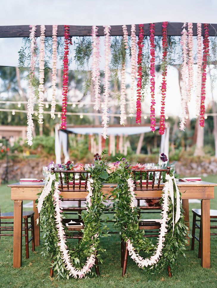 Chairs at the couple's sweetheart table were draped with white flower lei, greenery and lace.