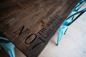 Rustic Wood Tables with Venue Inscription