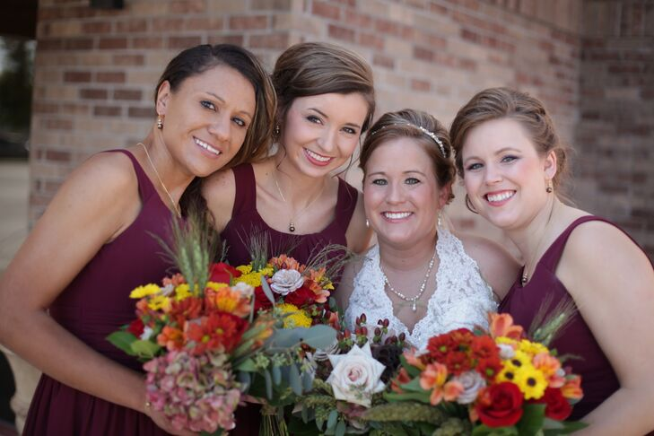 """The bridesmaids wore knee-length maroon colored dresses by D'Zage,"" Ashleigh says. They also carried bright, rustic bridesmaid bouquets."