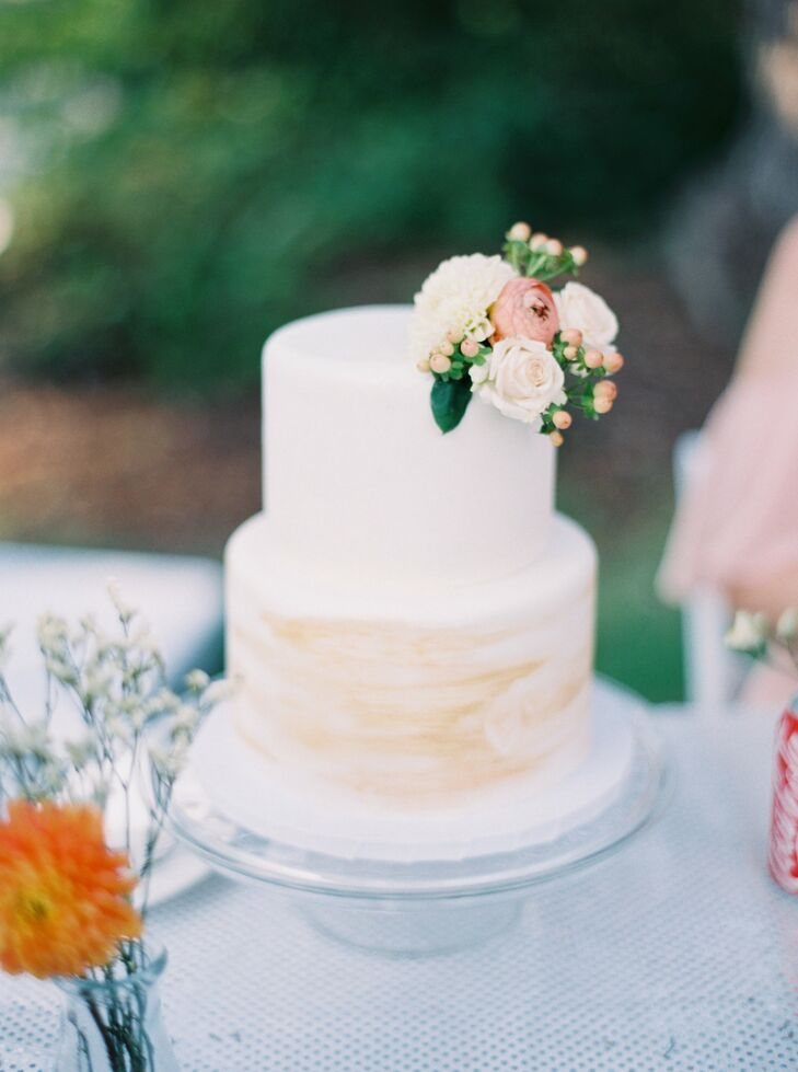 Simple Slice bakery created a two-tier ivory-hued cutting cake for Alison and Daniel. It was topped with a few blush blossoms.