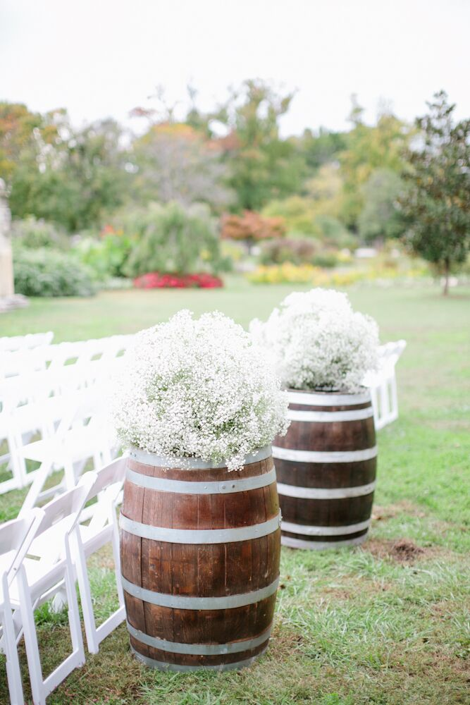"""The ceremony aisle was framed with two dark-wood wine barrels topped with lush, overflowing white baby's breath arrangements. """"Growing up I loved spending time on our front porch, surrounded by my mom's garden and birds enjoying food from the bird feeder,"""" Jessica says. """"I wanted my wedding to feel like I was sitting in my mom's garden."""""""