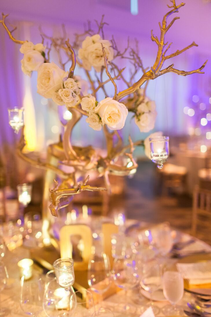 Kendal and Christopher liked the idea of height on the reception tables so they used tall gold metal manzanita trees as the centerpieces and mixed them with votives and ivory flowers. The height of the centerpieces made a noticeable impact against the tall ceilings.