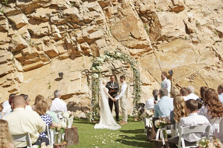 Ashlee and Dallan exchanged their vows in front of a red rock wall backdrop at Louland Falls. A wedding arch, draped with greenery and an asymmetrical arrangement of white flowers, along with white flower petals down the aisle, softened the outdoor venue.