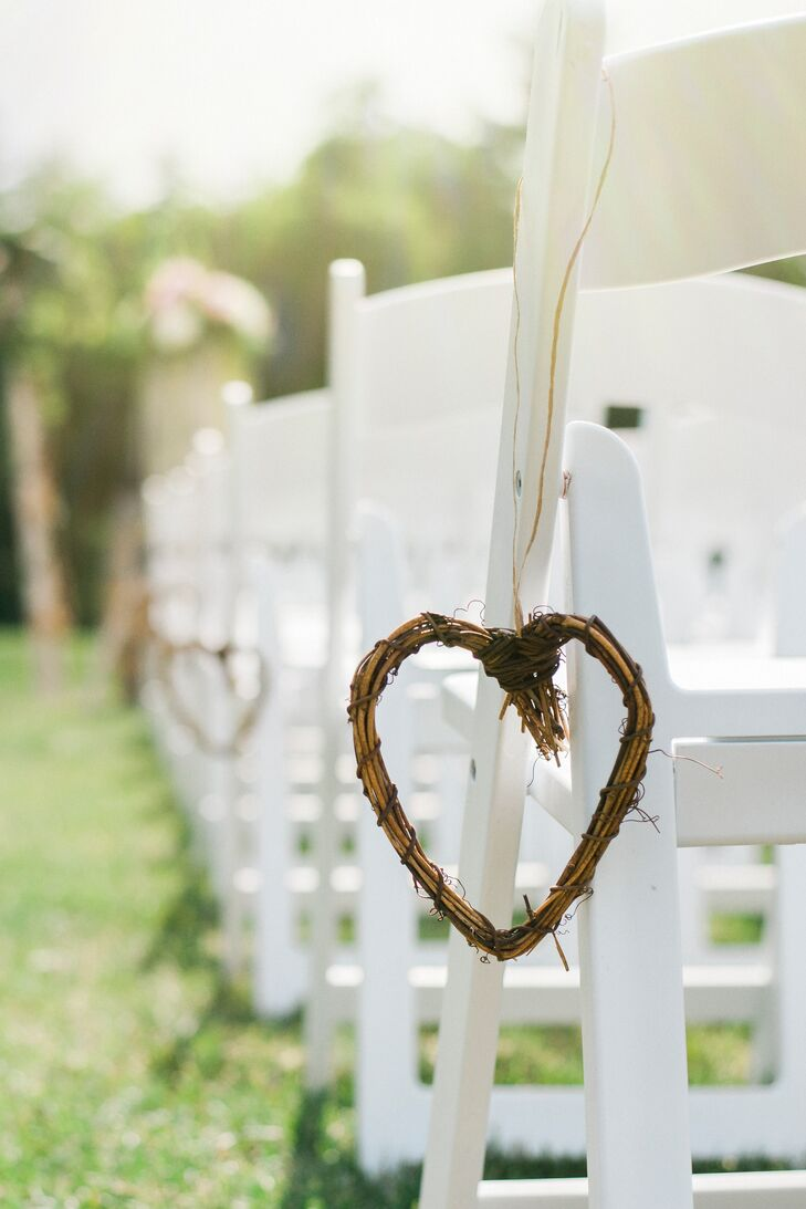 Wooden twig hearts hung from white ceremony chairs.