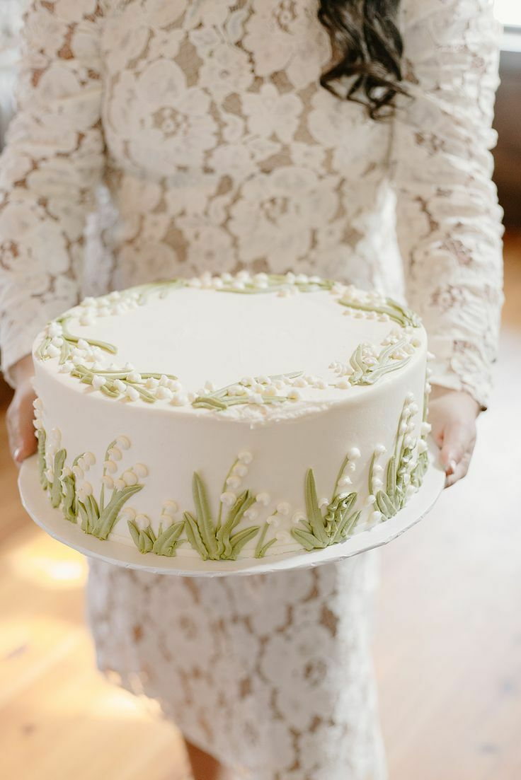 Simple white cake with lily of the valley decorations