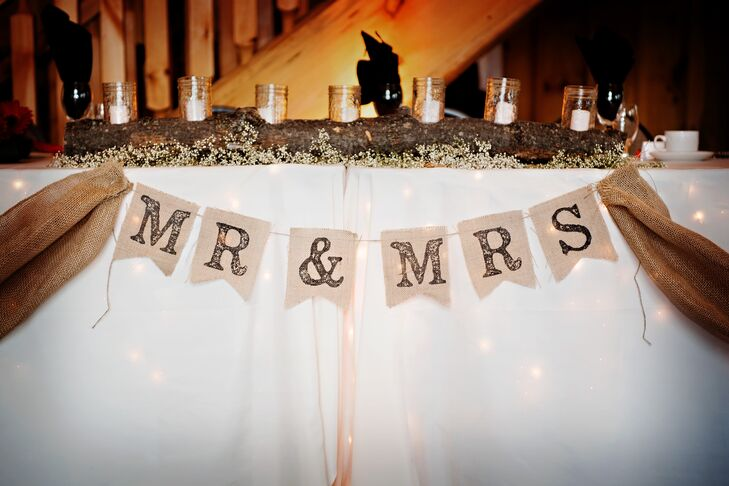 "A burlap sign that said ""Mr. & Mrs."" was hung in front of the main table at the reception. The rustic centerpiece was a large log with candles in mason jars embedded across the top."