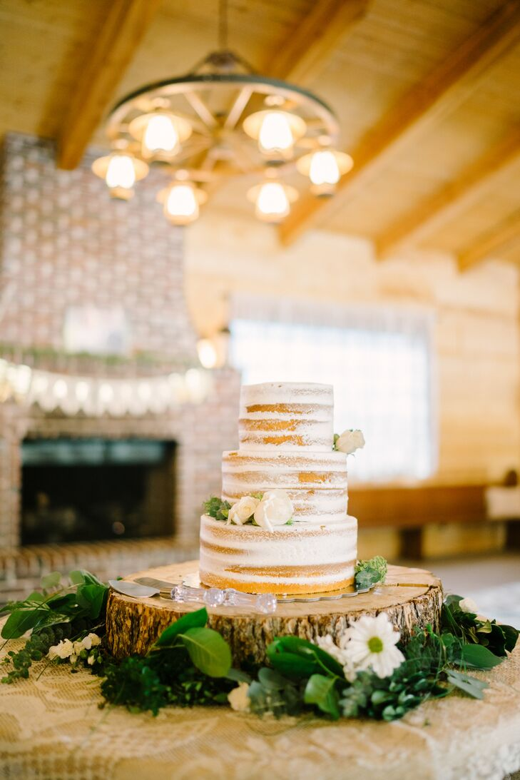 Cake Bliss of Provo, Utah, created Kourtney and Vasa's simple, roughly frosted white wedding cake adorned with white roses and displayed on a rustic wooden serving stand.